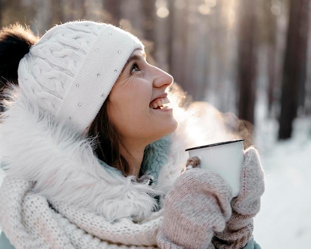 Smiley vrouw buiten in de winter met een kopje thee Premium Foto