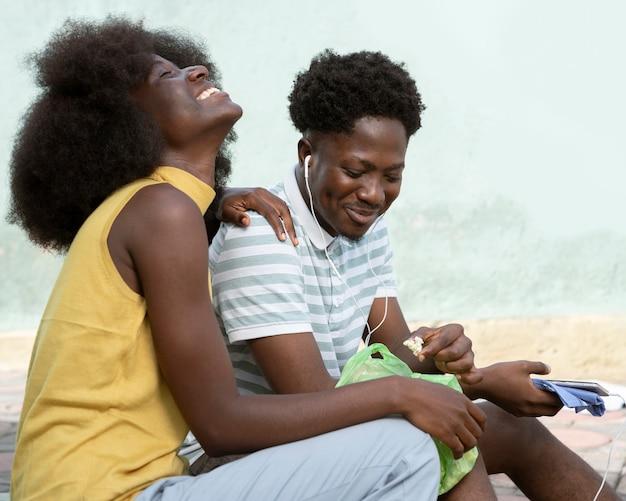 Smiley vrouw en man luisteren naar muziek Gratis Foto