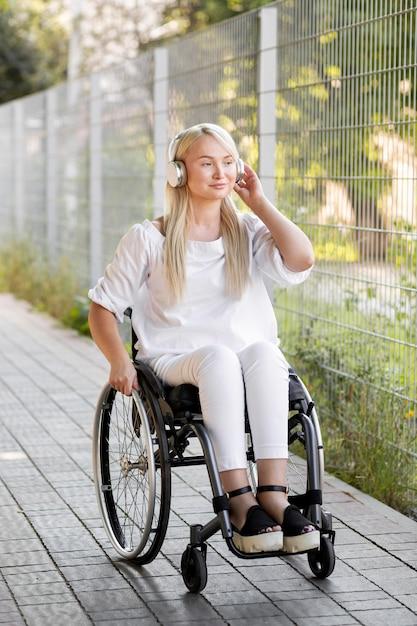Smiley vrouw in rolstoel met koptelefoon buitenshuis Gratis Foto