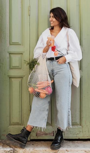 Smiley vrouw met boodschappentassen met frisdrank buitenshuis Gratis Foto