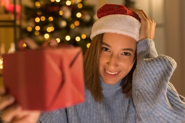 Smiley vrouw met kerstmuts met kerstcadeau Gratis Foto