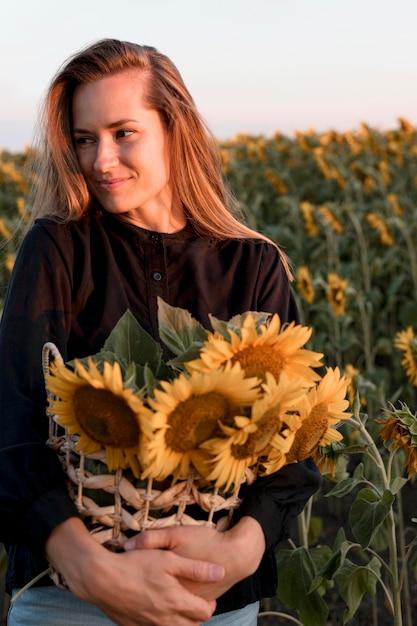 Smiley vrouw poseren met zonnebloemen mand Premium Foto