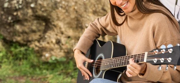 Smiley vrouw zittend in de kofferbak van de auto terwijl op een road trip en gitaar spelen Premium Foto