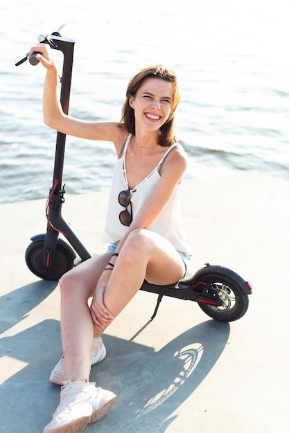Smiley vrouw zittend op scooter Gratis Foto