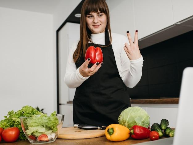Smiley vrouwelijke blogger streaming koken met laptop Gratis Foto