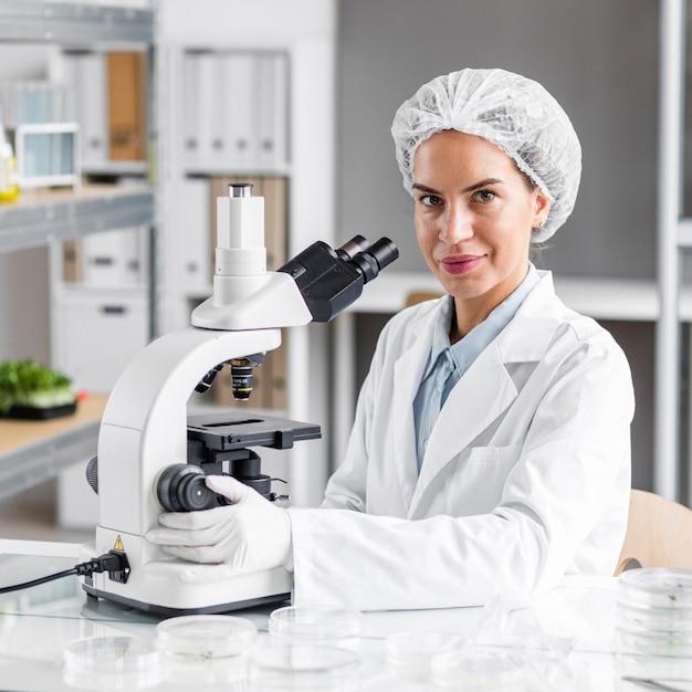Smiley vrouwelijke onderzoeker in het laboratorium voor biotechnologie met microscoop Premium Foto