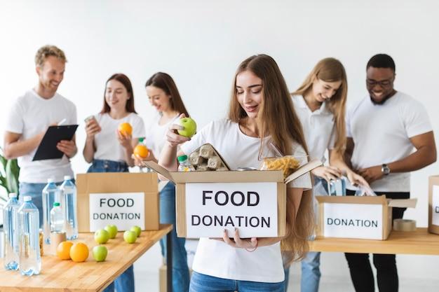 Smiley vrouwelijke vrijwilliger bedrijf doos met donaties Gratis Foto
