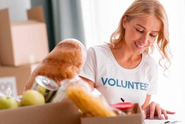 Smiley vrouwelijke vrijwilliger die helpt met voedseldonaties Gratis Foto
