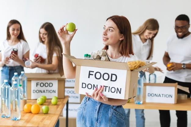 Smiley vrouwelijke vrijwilliger die voedseldonatiesdoos met appel houdt Gratis Foto
