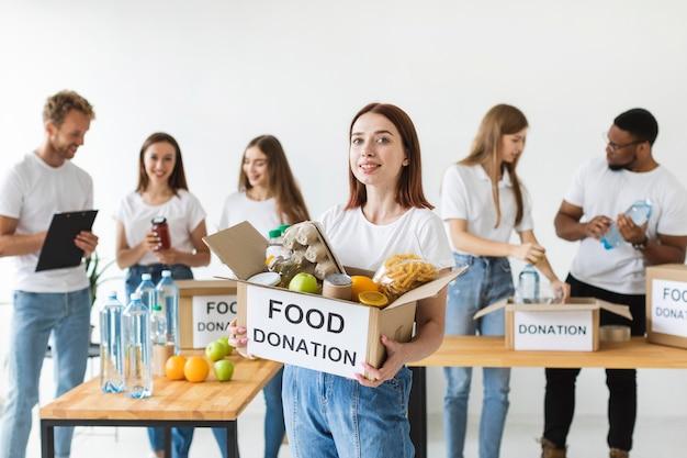 Smiley vrouwelijke vrijwilliger donatiebox met voedsel te houden Gratis Foto