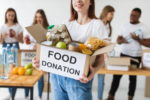 Smiley vrouwelijke vrijwilliger donaties doos met voedsel te houden Gratis Foto