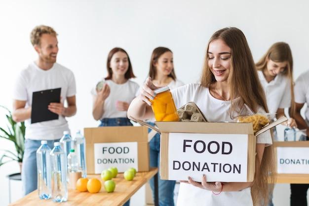 Smiley vrouwelijke vrijwilliger en vrienden die voedseldonaties houden Gratis Foto