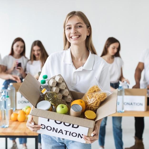 Smiley vrouwelijke vrijwilliger met voedseldonaties Premium Foto