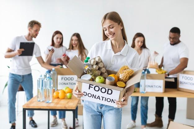 Smiley vrouwelijke vrijwilliger voedseldonaties in doos te houden Gratis Foto
