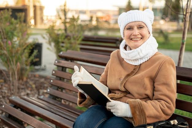Smiley vrouwelijke zittend op een bankje en lezen Gratis Foto