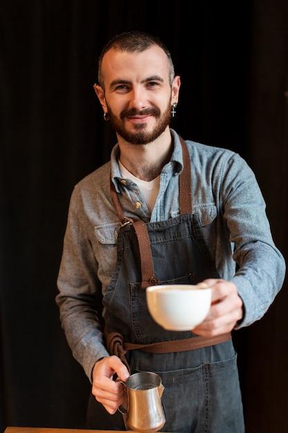 Smiley-werknemer die koffie maakt Gratis Foto