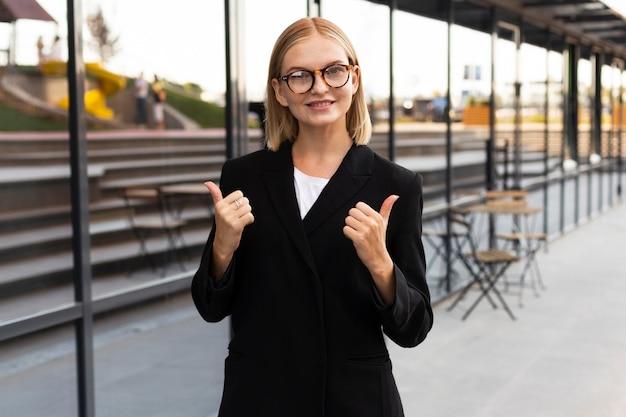 Smiley zakenvrouw met gebarentaal buitenshuis op het werk Gratis Foto