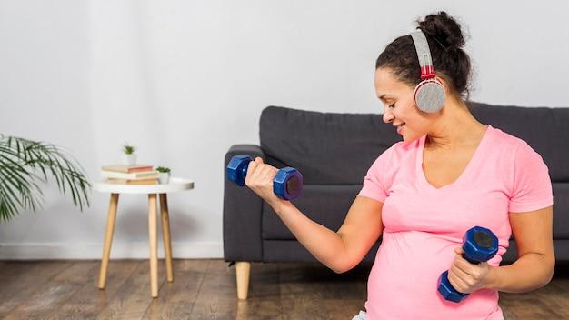 Smiley zwangere vrouw luisteren naar muziek op de koptelefoon tijdens het trainen met gewichten Gratis Foto