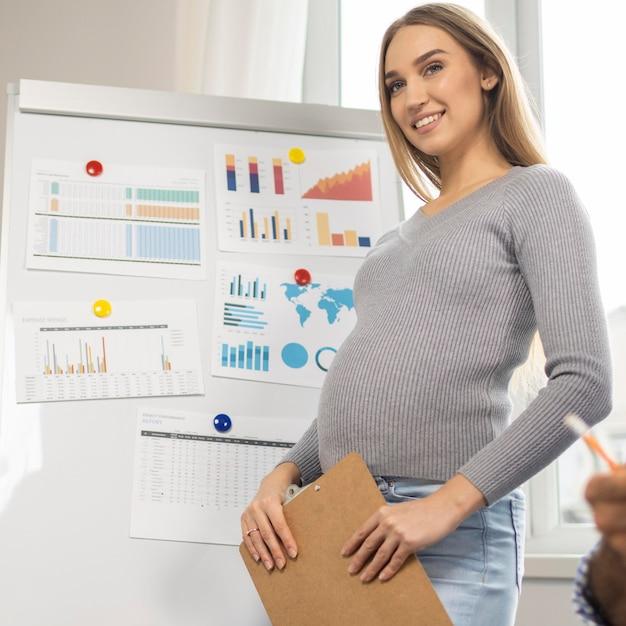 Smiley zwangere zakenvrouw klembord houden tijdens de presentatie op kantoor Premium Foto