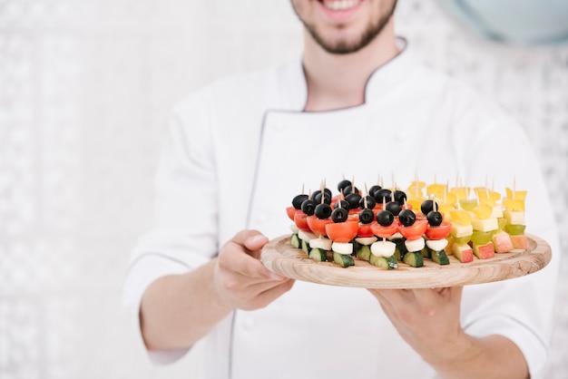 Smileychef-kok in eenvormige holdingssnacks Gratis Foto
