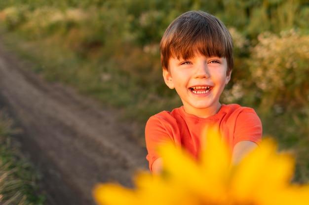 Smileyjong geitje met gele bloem Gratis Foto