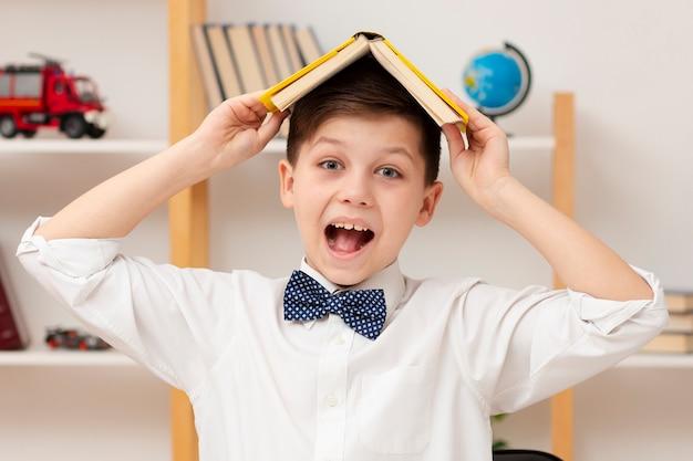 Smileyjongen met boek op zijn hoofd Gratis Foto