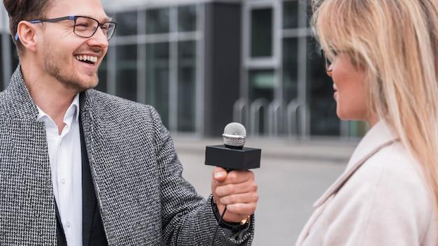Smileyjournalist die interview doet Gratis Foto