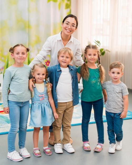 Smileyleraar houdt haar studenten vast voor een foto Gratis Foto
