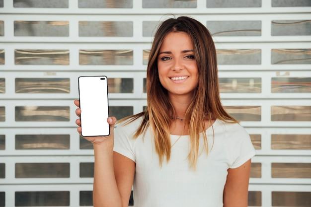 Smileymeisje die cellphone met model tonen Gratis Foto