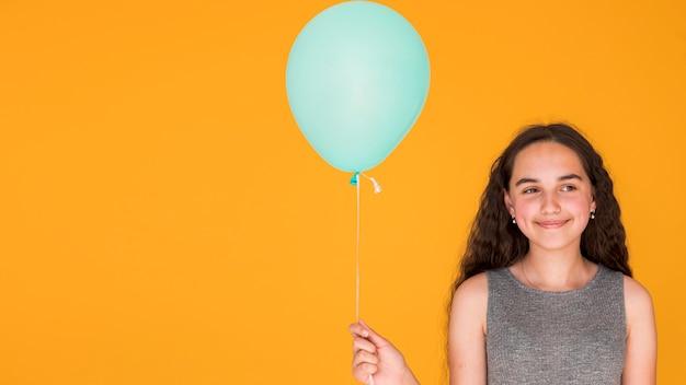 Smileymeisje die een blauwe ballon met exemplaarruimte houden Gratis Foto