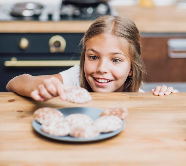 Smileymeisje die een heerlijk koekje nemen Gratis Foto