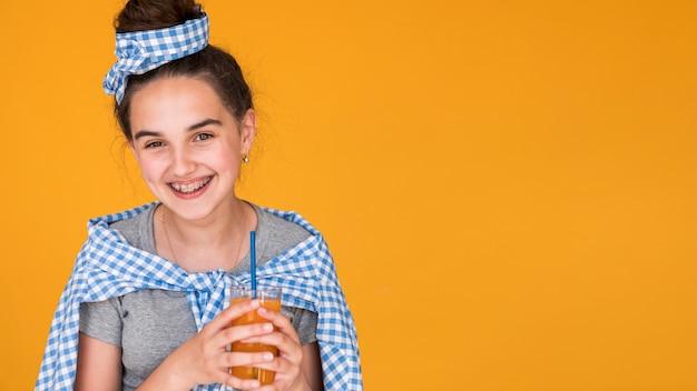 Smileymeisje die van haar jus d'orange genieten Gratis Foto