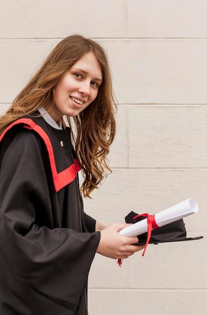 Smileymeisje met afgestudeerd diploma Gratis Foto
