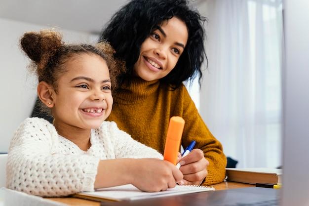 Smileymeisje thuis tijdens online school met grote zus Premium Foto