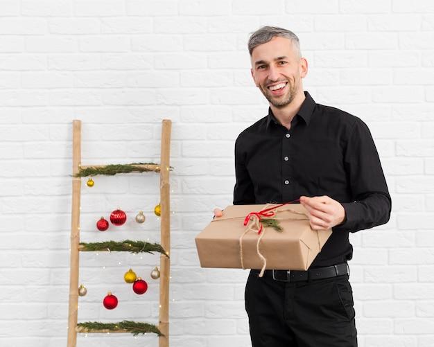 Smileymens die een gift naast een ladder met kerstmisvoorwerpen uitpakken Gratis Foto