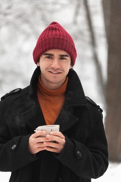 Smileymens die rode hoed dragen en kop thee houden Gratis Foto