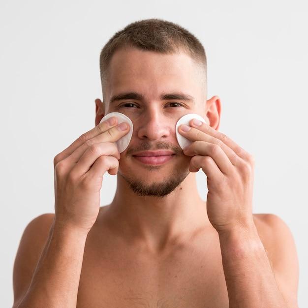 Smileymens die wattenschijfjes op zijn gezicht gebruikt Gratis Foto