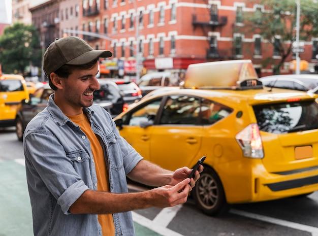 Smileymens in stad mobiel houden Gratis Foto