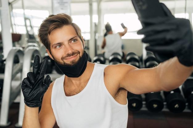 Smileymens met medisch masker die een selfie in de gymnastiek nemen Premium Foto