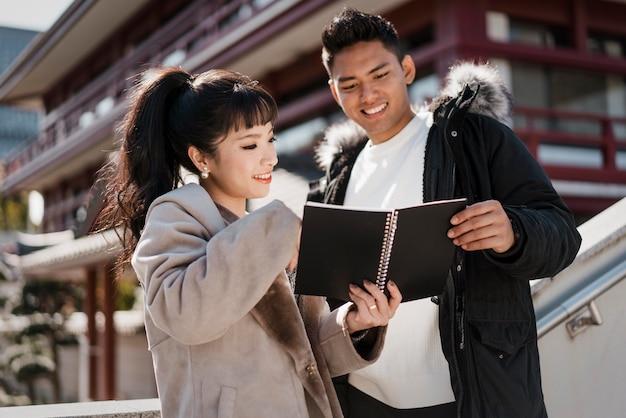 Smileypaar dat samen een notitieboekje bekijkt Gratis Foto