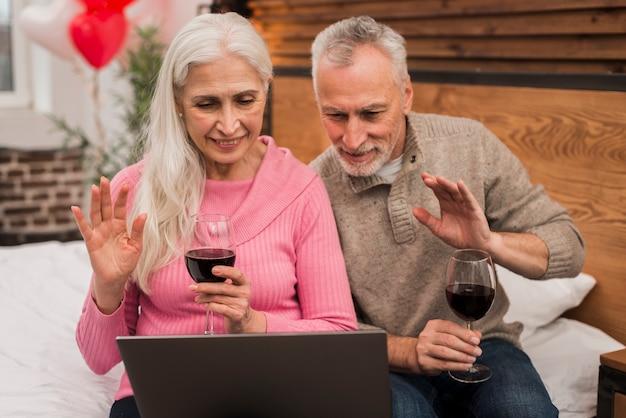 Smileypaar gebruikend laptop en drinkend wijn Gratis Foto