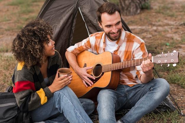 Smileypaar gitaarspelen tijdens het kamperen buiten Gratis Foto