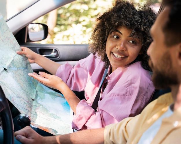 Smileypaar in auto raadplegende kaart Gratis Foto
