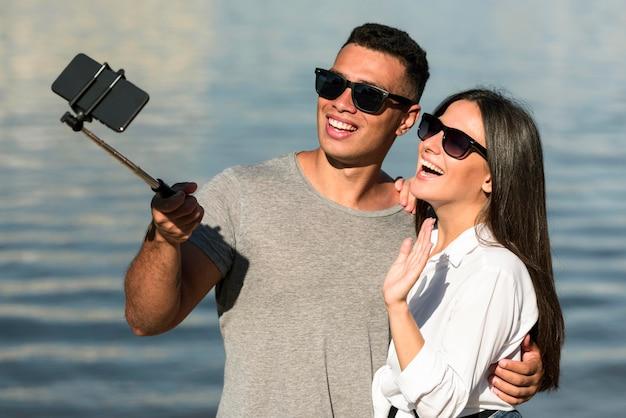 Smileypaar met zonnebril die selfie op het strand nemen Gratis Foto