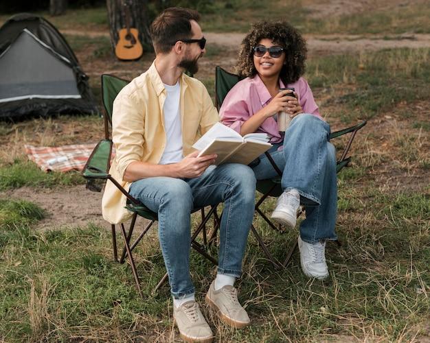 Smileypaar met zonnebril lezen en drinken tijdens het kamperen buiten Gratis Foto
