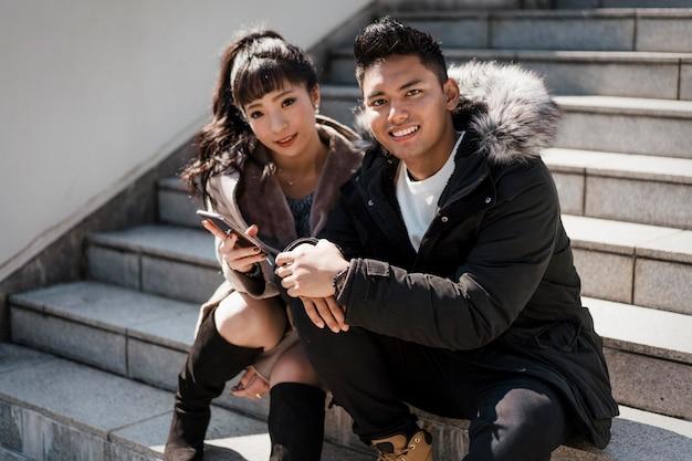 Smileypaar zittend op trappen met smartphone Gratis Foto