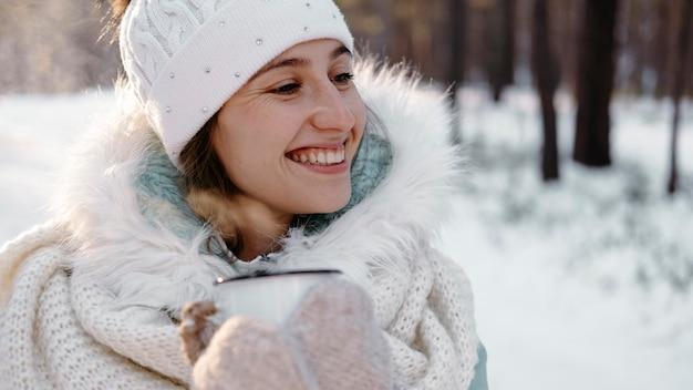 Smileyvrouw buiten in de winter met een kopje thee Premium Foto