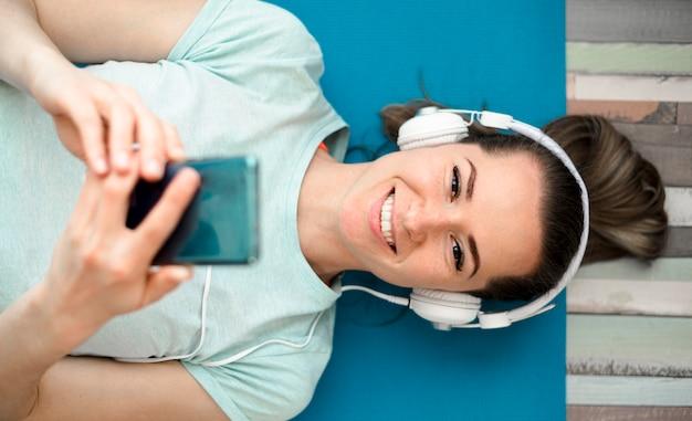 Smileyvrouw die aan muziek luisteren terwijl het uitwerken Gratis Foto