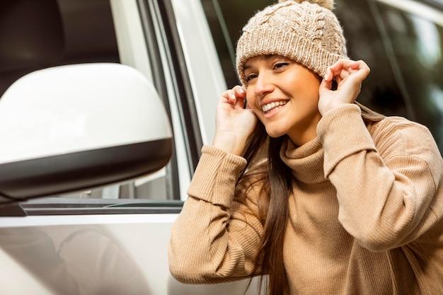 Smileyvrouw die beanie opzet tijdens een roadtrip Premium Foto