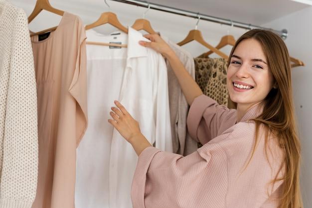 Smileyvrouw die beslist wat te dragen Gratis Foto